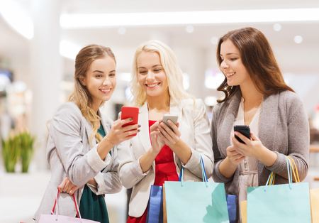 sale, consumerism, technology and people concept - happy young women with smartphones and shopping bags in mall photo