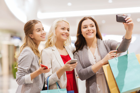 sale, consumerism, technology and people concept - happy young women with smartphones and shopping bags taking selfie in mall photo