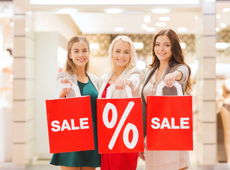 consumerism and people concept - happy young women holding shopping bags with sale and percentage sign in mall photo