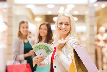sale, consumerism and people concept - happy young women with shopping bags and euro cash money in mall photo