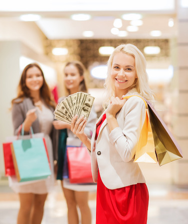 sale, consumerism and people concept - happy young women with shopping bags and usa dollar cash money in mall photo