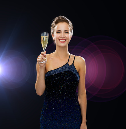 party, drinks, holidays, people and celebration concept - smiling woman in evening dress with glass of sparkling wine over night lights 版權商用圖片
