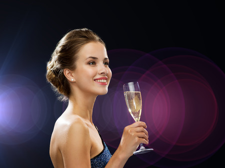 party, drinks, holidays, people and celebration concept - smiling woman in evening dress with glass of sparkling wine over night lights Stok Fotoğraf