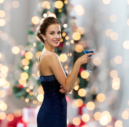 パーティー、ドリンク、祝日、人々 とお祝いのコンセプト - クリスマス ツリー ライト背景上カクテル開催のイブニング ドレスの女性を笑顔 写真素材
