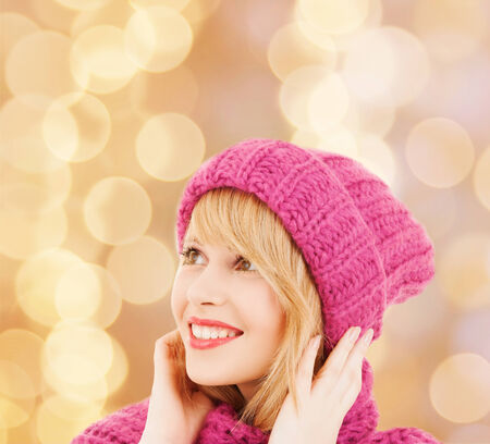 head wear: happiness, winter holidays, christmas and people concept - smiling young woman in pink hat and scarf over beige lights background Stock Photo