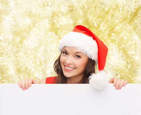 christmas, x-mas, people, advertisement and sale concept - happy woman in santa helper hat with blank white board over yellow lights background photo