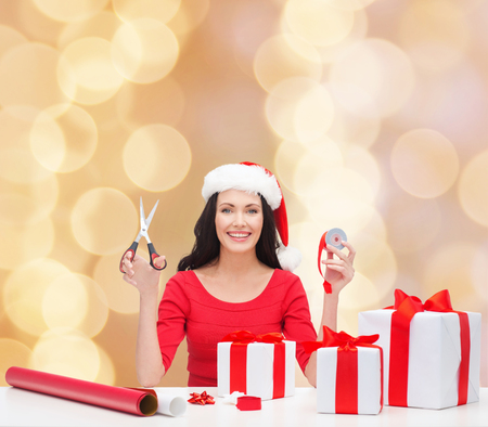 christmas, holidays, celebration, decoration and people concept - smiling woman in santa helper hat with scissors packing gift boxes over beige lights  photo