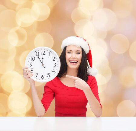 christmas, winter, holidays, time and people concept - smiling woman in santa helper hat and red dress with clock over beige lights  Stock Photo