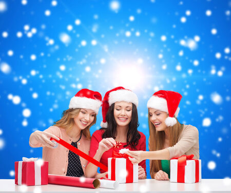 christmas, holidays, celebration, decoration and people concept - smiling women in santa helper hats with decorating paper and gift boxes over blue snowy  photo