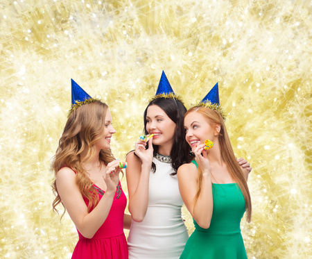 noisemaker: holidays, people and celebration concept - smiling women in party caps blowing to whistles over yellow lights background