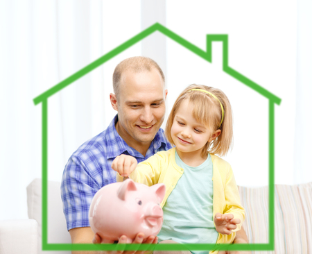 human energy: family, children, money, investments and happy people concept - happy father and daughter with big pink piggy bank behind green house symbol