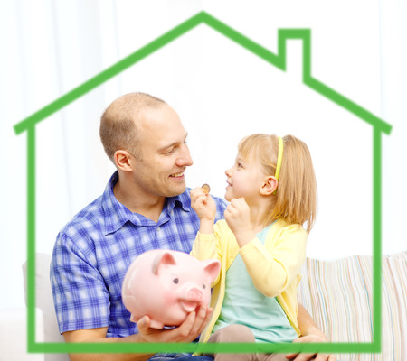 family budget: family, children, money, investments and happy people concept - happy father and daughter with big pink piggy bank behind green house symbol