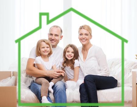 familie, kinderen, accommodatie en home concept - lachende ouders en twee kleine meisjes thuis achter groen huis symbool Stockfoto