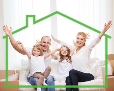 家族、子供、宿泊施設とホーム コンセプト - 両親と 2 人の少女自宅で緑の家の記号の後ろに笑みを浮かべて