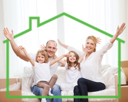 energy savings: family, children, accommodation and home concept - smiling parents and two little girls at home behind green house symbol