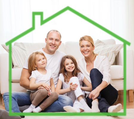family, children, accommodation and home concept - smiling parents and two little girls at home behind green house symbol
