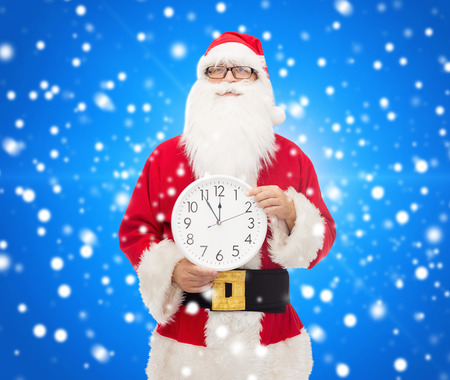 christmas, holidays and people concept - man in costume of santa claus with clock showing twelve pointing finger over blue snowy