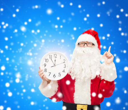 twelve month old: christmas, holidays and people concept - man in costume of santa claus with clock showing twelve pointing finger up over blue snowy