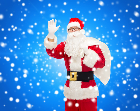 christmas, holidays, gesture and people concept - man in costume of santa claus with bag waving hand over blue snowy background photo