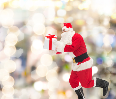 nicolas: christmas, holidays and people concept - man in costume of santa claus running with gift box over lights background