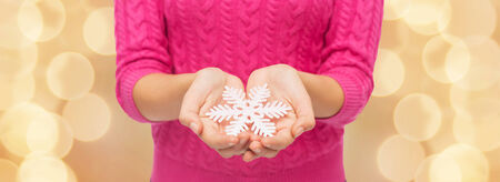 christmas, holidays and people concept - close up of woman in pink sweater holding snowflake over beige lights background photo