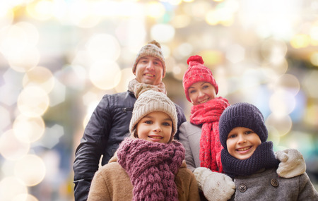 family, childhood, season, holidays and people concept - happy family in winter clothes over lights