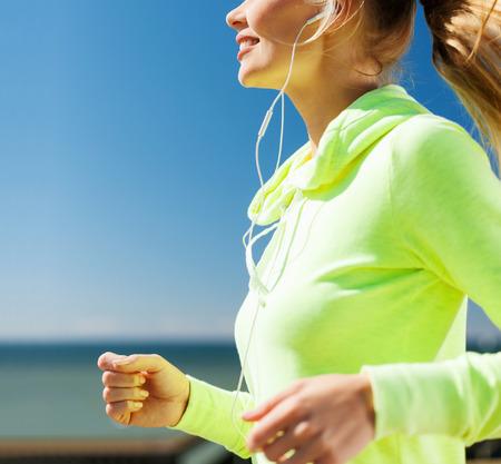 sport en een gezonde levensstijl concept - vrouw lopen en muziek luisteren met een koptelefoon buiten