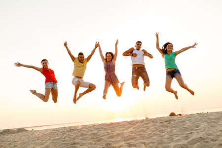friendship, summer vacation, holidays, party and people concept - group of smiling friends dancing and jumping on beach 免版税图像
