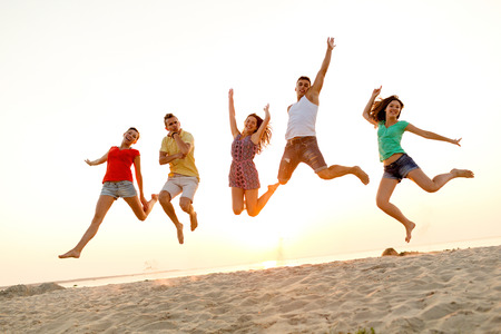 friendship, summer vacation, holidays, party and people concept - group of smiling friends dancing and jumping on beach photo