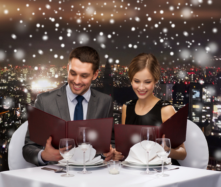 couple dining: food, christmas, holidays and people concept - smiling couple with menus at restaurant over snowy night city background