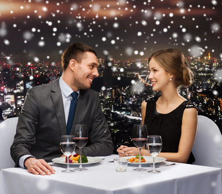 over eating: food, christmas, holidays and people concept - smiling couple eating main course at restaurant over snowy night city background