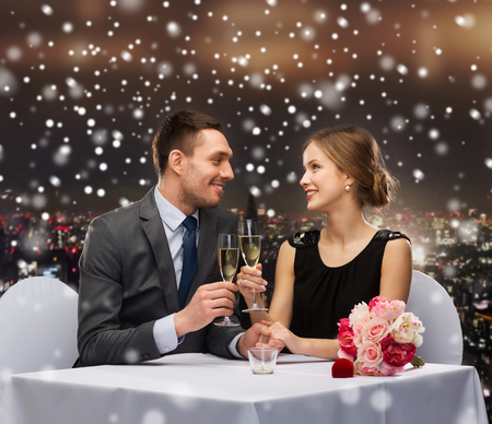 celebration, christmas, holidays and people concept - smiling couple clinking glasses of sparkling wine at restaurant over snowy night city background photo