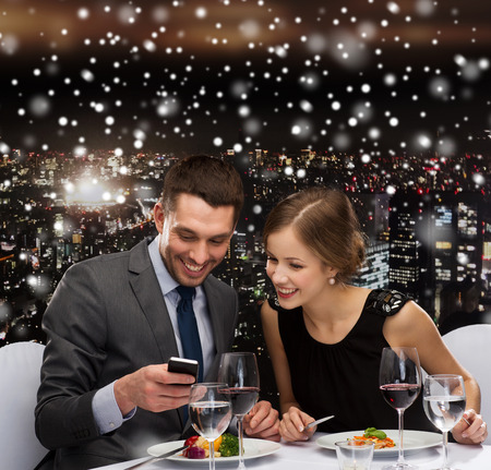 technology, food, christmas, holidays and people concept - smiling couple with smartphone eating at restaurant over snowy night city background photo