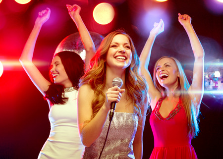 new year, celebration, friends, bachelorette party, birthday concept - three women in evening dresses dancing and singing karaoke photo