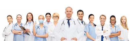 medicine, profession, teamwork and healthcare concept - international group of smiling medics or doctors with clipboard and stethoscopes over white