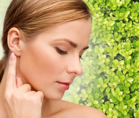beauty, people and ecology concept - beautiful young woman touching or pointing finger to ear over green background Stock Photo
