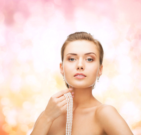 string of pearls: beauty, people and jewelry concept - beautiful woman with pearl earrings and necklace over pink lights background Stock Photo