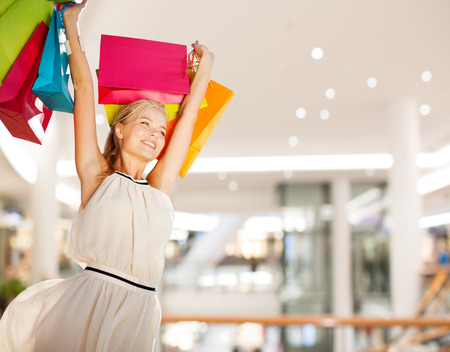 consumerism: happiness, consumerism, sale and people concept - smiling young woman with shopping bags over mall background