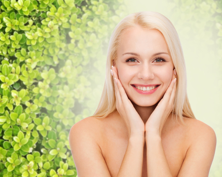 eco sensitive: beauty, people and ecology concept - beautiful young woman touching her face skin over green background Stock Photo
