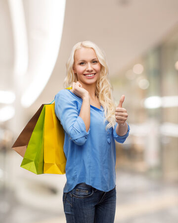 happiness, consumerism, sale and people concept - smiling young woman with shopping bags showing thumbs up gesture over mall background photo