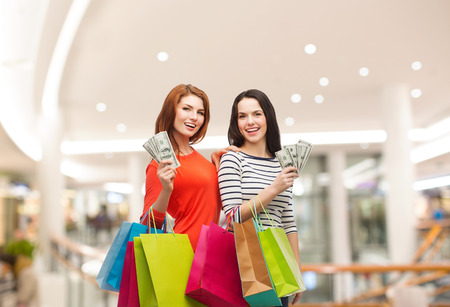 sale, friendship and people concept - two smiling teenage girls with shopping bags and cash money over mall background photo