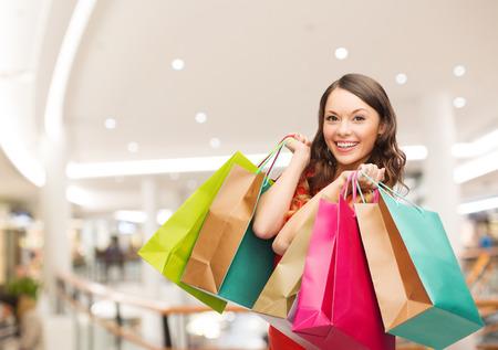 幸福、消費者、販売人のコンセプト - モールの背景の上のショッピング バッグを持つ若い女性の笑顔