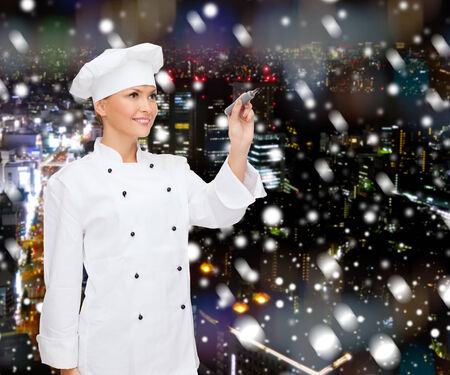 cooking, holidays, advertisement and people concept - smiling female chef, cook or baker with marker writing something on virtual screen over snowy night city background photo