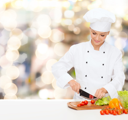 young knife: cooking, holidays, people and food concept - smiling female chef chopping vegetables over lights