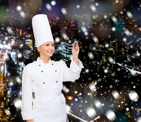 cooking, holidays, advertisement and people concept - smiling female chef, cook or baker with marker writing something on virtual screen over snowy night city  photo