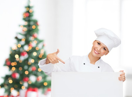 christmas cooking: cooking, advertisement, holidays and people concept - smiling female chef, cook or baker pointing finger to white blank board over living room and christmas tree background Stock Photo