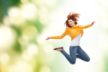 happiness, freedom, movement and people concept - smiling young woman jumping high in air over green