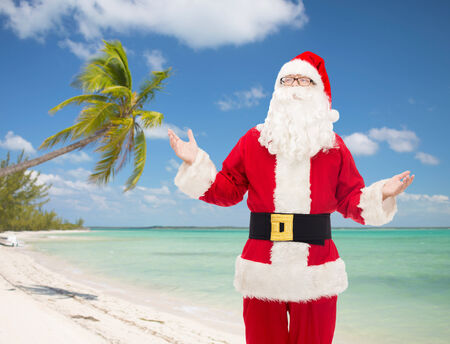 christmas, holidays, travel and people concept - man in costume of santa claus over tropical beach