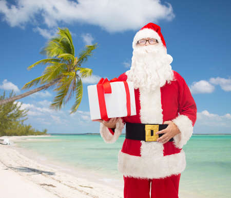christmas, travel, holidays and people concept - man in costume of santa claus with gift box over tropical beach background photo