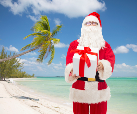 christmas, travel, holidays and people concept - man in costume of santa claus with gift box over tropical beach  photo
